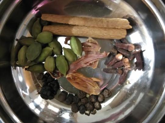 一番上から時計回りに、シナモン、クローブ、黒コショウ、ブラックカルダモン、グリーンカルダモン、   中心の赤茶色の物はメース